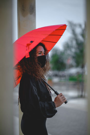 Woman holding umbrella standing during rainy season