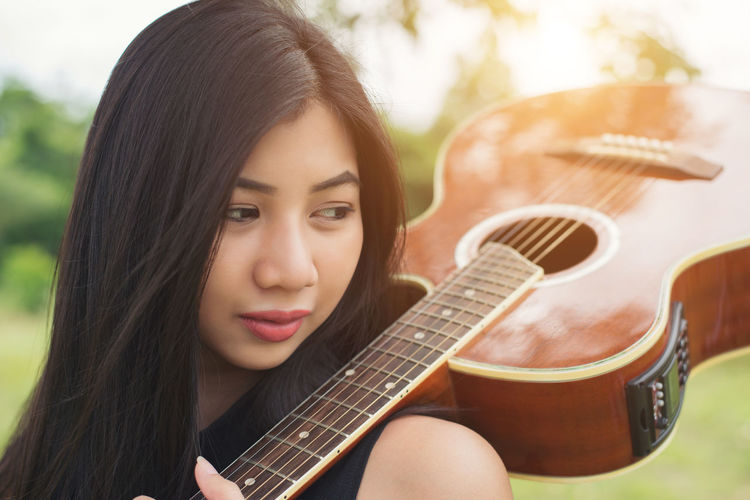 Close-up of young woman holding guitar