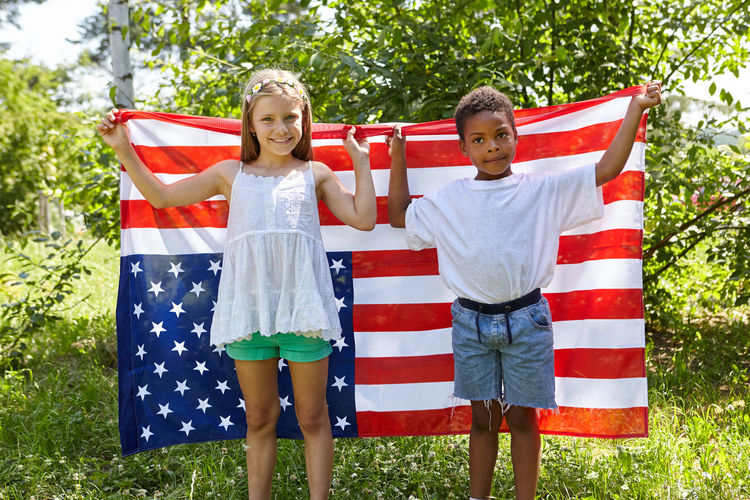 portrait of a smiling girl standing against flag Adopted Child America American Blond Boy Child Childhood Children Couple Emotion Family Females Flag Foster-child Freedom Friends Friendship Front View Girl Girls Happiness Happy Integration International Interracial Kids Kindergarten Leisure Looking At Camera Men Nation National Pride Nature North America Outdoors Patchwork Family Patriotic Patriotism People Portrait Positive Emotion Preschool Proud Smiling STAND Standing Stars Stars And Stripes Stepchild Summer Symbol Team Teamwork Together Togetherness USA Women Young