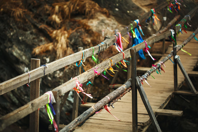 Wooden bridge above mountain river in autumn with traditional buddhism ribbons. nature background.