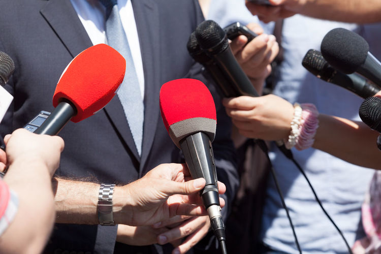 Cropped Image Of Reporters Taking Interview Of Speaker