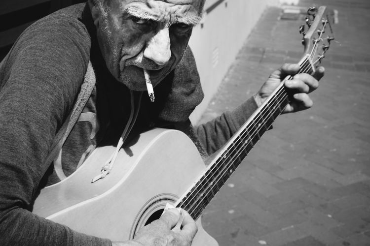 Busker playing a Rodriguez song in town. Bet he has some stories to tell Blackandwhite Busker Candid Casual Clothing Cigarette  Guitar Holding Homeless Outdoors Real Life Street Streetphotography The Street Photographer - 2017 EyeEm Awards