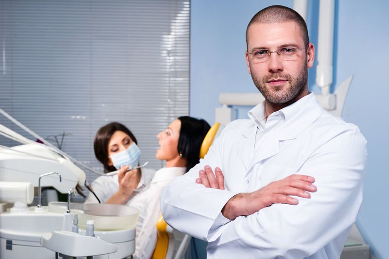 Portrait of confident male doctor with coworker operating patient in background at dental clinic