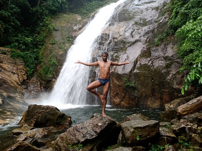 Full length of shirtless man standing on rock against waterfall in forest