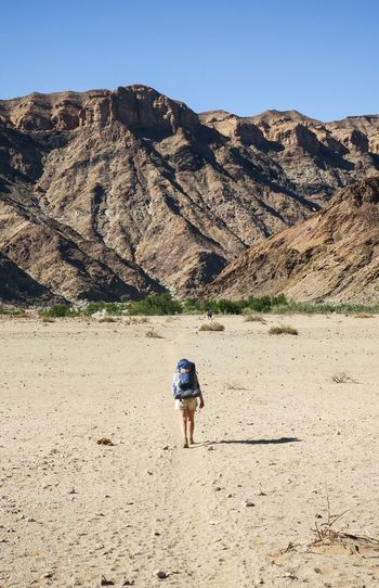 Female hiker walking along sandy path towards scenic mountain range Adventure Arid Climate Backpack Bag Clear Sky Desert Explore Hike Hiker Hiking Landscape Landscape_Collection Let's Go. Together. Mountain Mountain Range Nature Nature One Person One Woman Only Outdoors Rear View Travel Walking