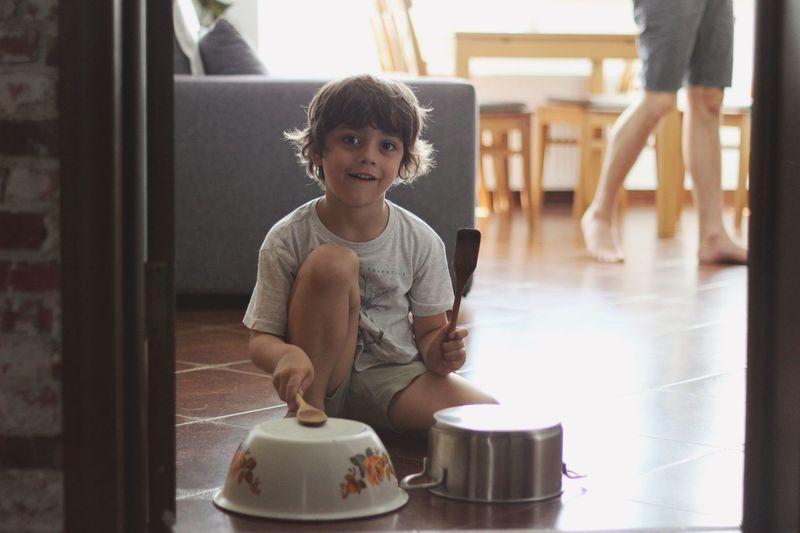 Portrait Of Cute Boy Banging Kitchen Utensils At Home