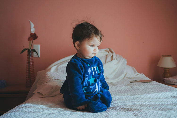 Cute boy sitting on bed at home