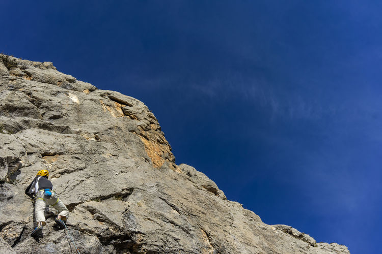 Low angle view of man on rock against blue sky