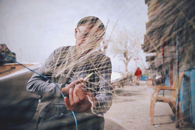 Man Cutting Fishing Net In City