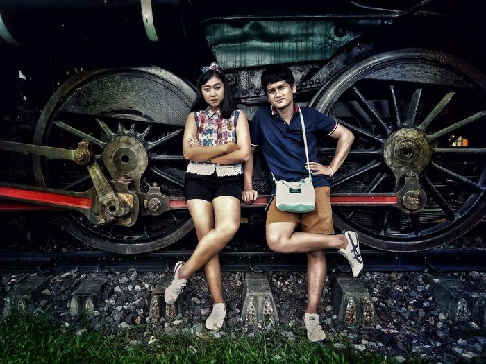 Portrait of young couple leaning on train