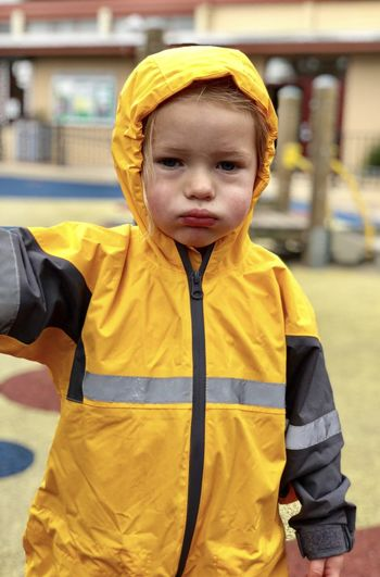 Portrait of boy wearing raincoat while standing outdoors