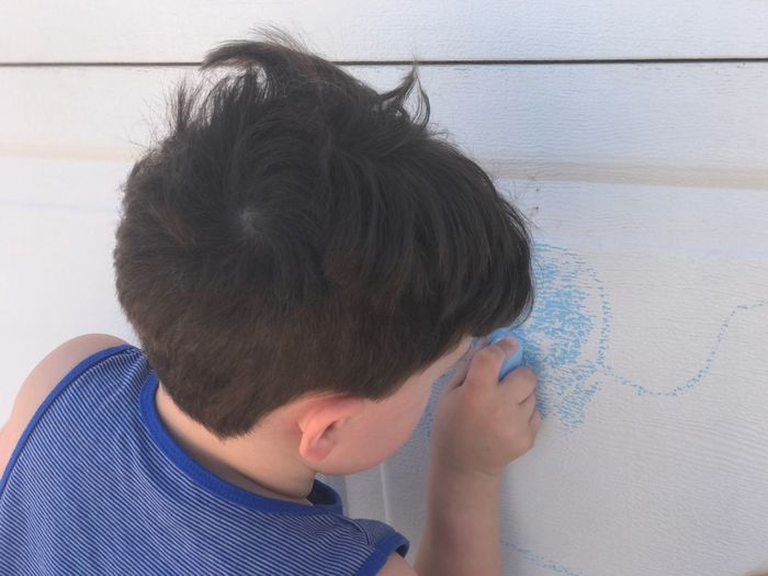 Close-up of boy drawing on wall