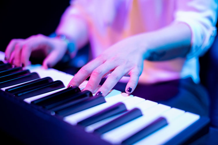 Close-up of human hand playing piano