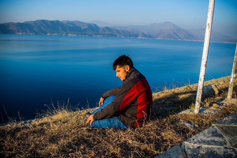 Thoughtful Man Sitting At Lakeshore Against Mountains
