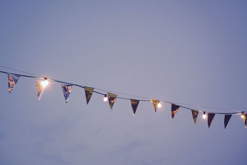 Low angle view of bunting flags with illuminated light bulbs against sky at dusk