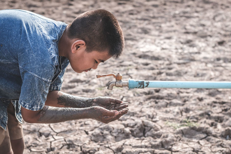Boy with dirty hands under tap on drought land