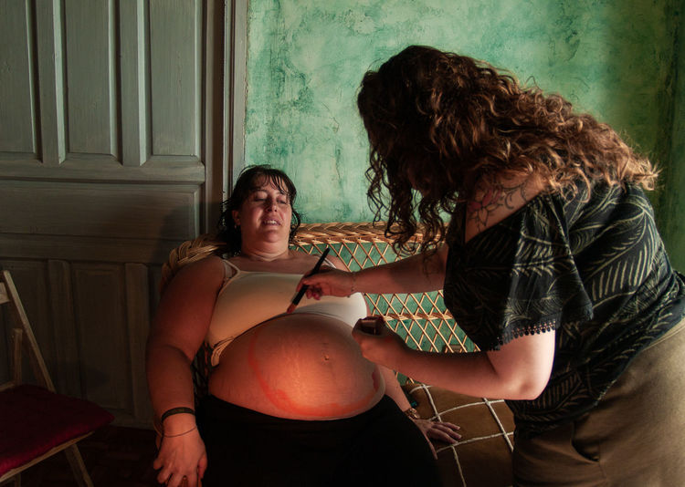 Woman Painting On Pregnant Belly At Home