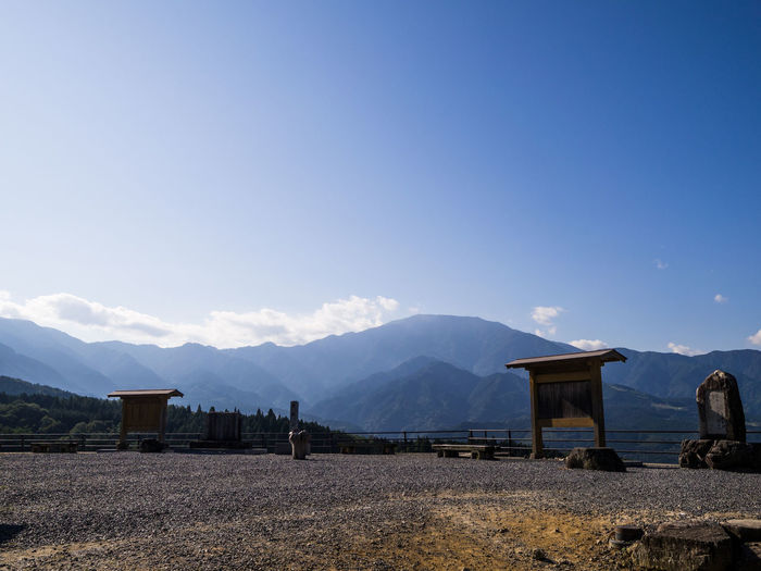 Built structure on field by mountains against blue sky