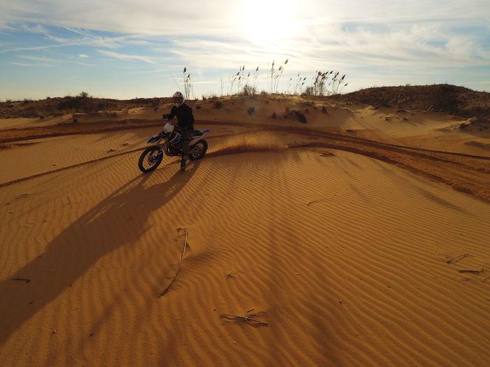 Man on sand at desert against sky during sunset