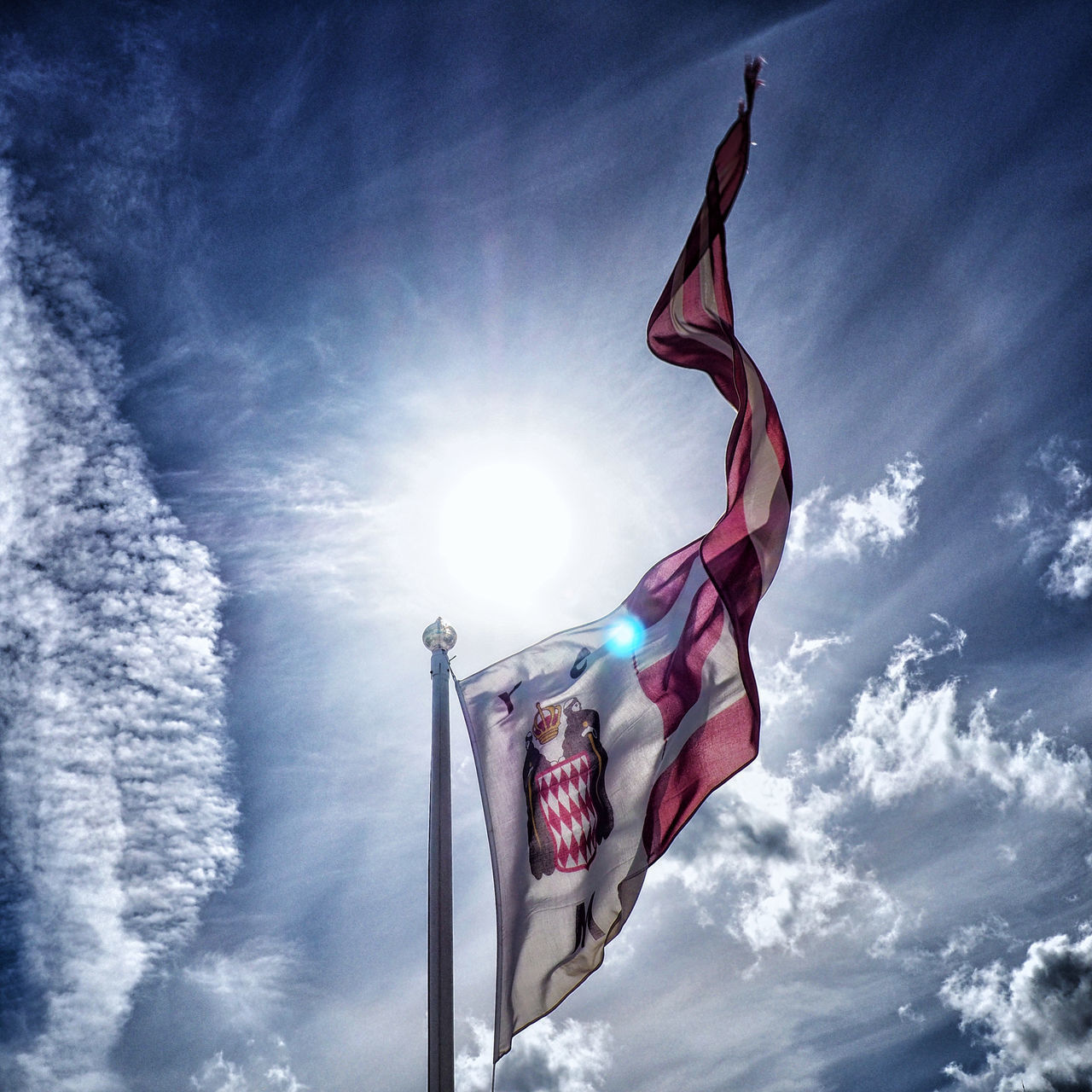 sky, cloud - sky, flag, low angle view, patriotism, sun, nature, sunlight, day, sunbeam, wind, no people, environment, outdoors, lens flare, pride, pole, blue, national icon, independence, bright