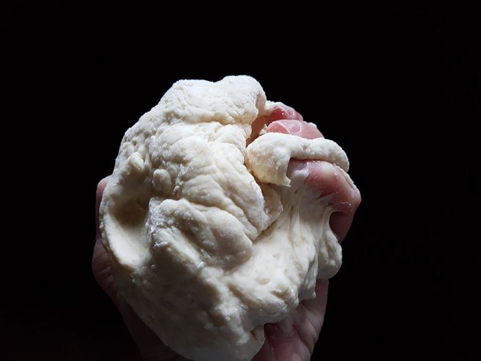 Cropped hand holding dough against black background
