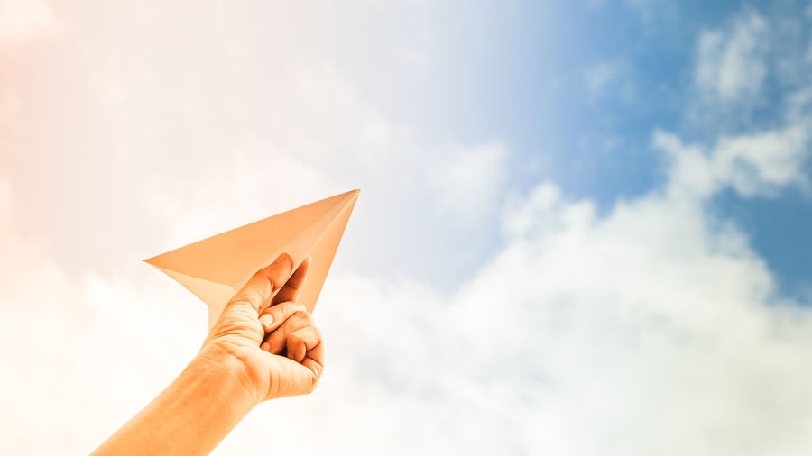 Close-up of hand holding paper airplane against sky