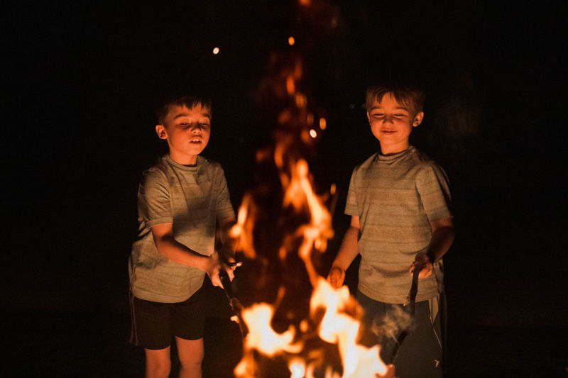 Full length of boy standing against fire at night