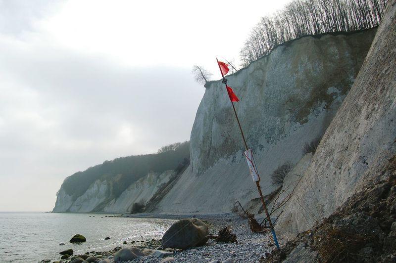 Flag by chalk cliff at beach against sky
