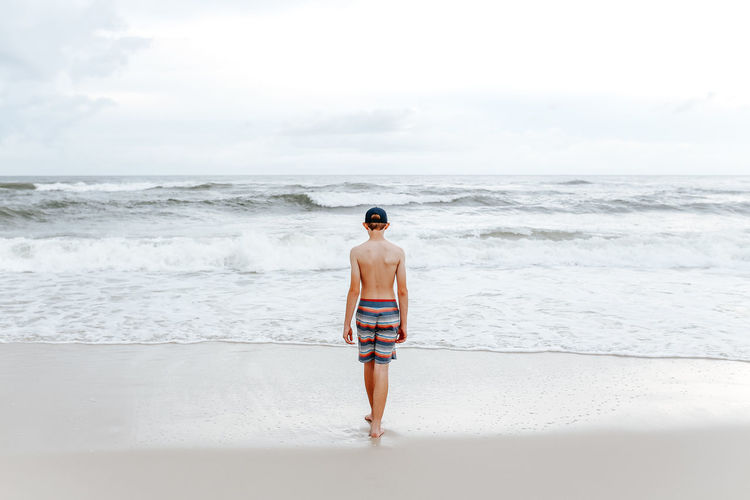Rear view of shirtless man standing on beach against sky
