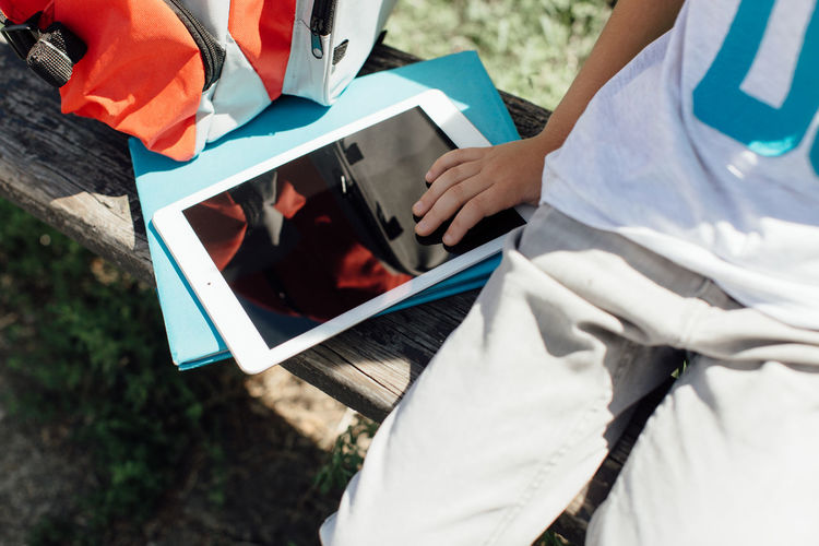 Cropped image of a student on a bench with a tablet and a schoolbag. Bench Horizontal Screen Tablet Back To School Black Caucasian Close Up Cropped Digital Hand Outdoors Schoolboy Sitting Technology Touching