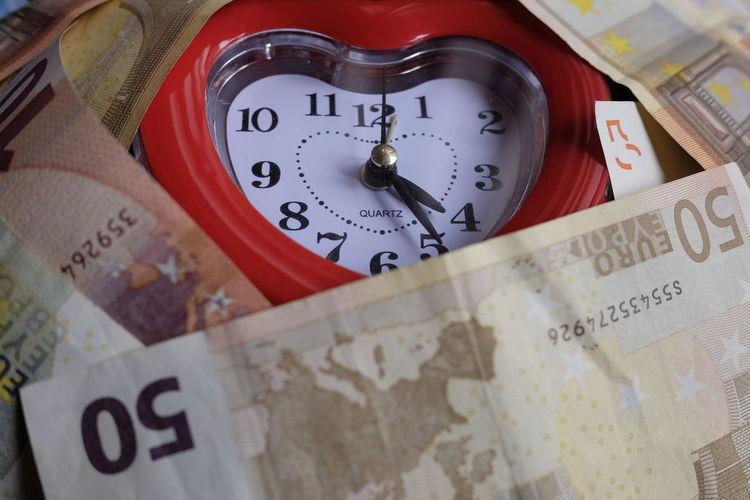 Close-up of heart shape alarm clock amidst european union currencies