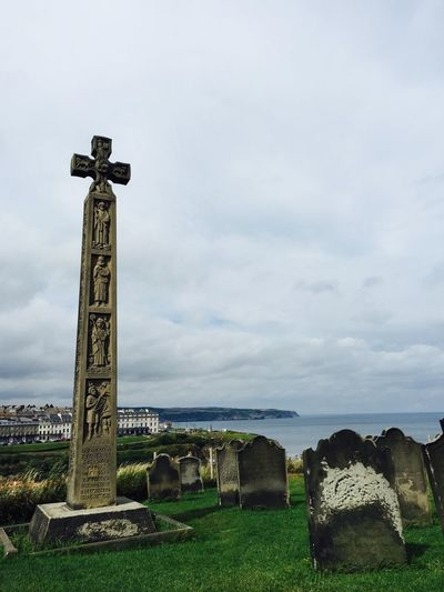Cross In Cemetery By Sea Against Cloudy Sky