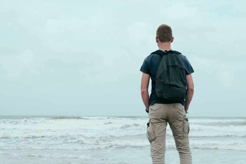 Young fit handsome man standing on beautiful exotic beach Beach Beauty In Nature Casual Clothing Contemplation Horizon Horizon Over Water Land Leisure Activity Lifestyles Looking At View Men Nature One Person Outdoors Real People Rear View Sea Sky Standing Three Quarter Length Water