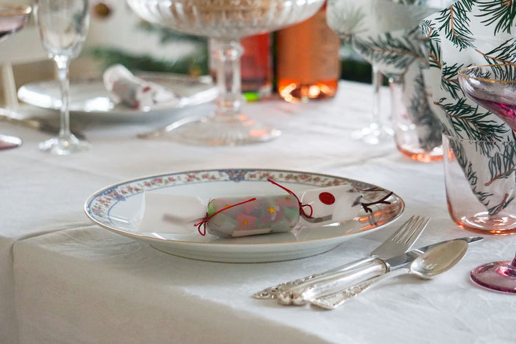 Close-up of table setting with plates and  wine glasses on table