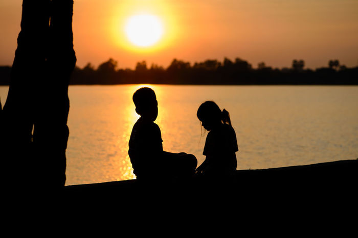 Adult Beauty In Nature Bonding Brother Childhood Lake Leisure Activity Nature Outdoors People Sea Sibling Silhouette Silhouette Sister Sitting Sky Sunset Sunset Silhouettes Together Togetherness Warm Colors Warmth Feeling Warmth Of The Sun Water