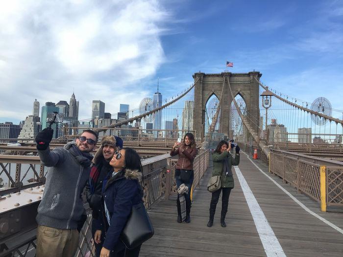 People on suspension bridge against cloudy sky