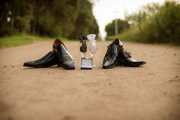 Wedding rings with shoes and wineglasses on land