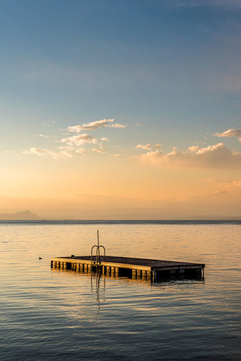 Floating platform on sea against sky during sunset