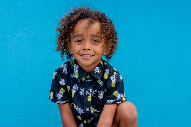 Firestarter Looking At Camera Portrait Smiling Childhood One Person Child Blue Front View Happiness Hairstyle Colored Background Women Curly Hair Innocence Cute Casual Clothing Studio Shot Emotion Blue Background Hair