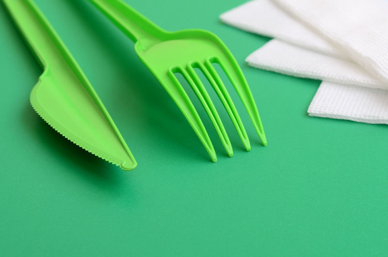 High angle view of plastic table knife and fork on green background