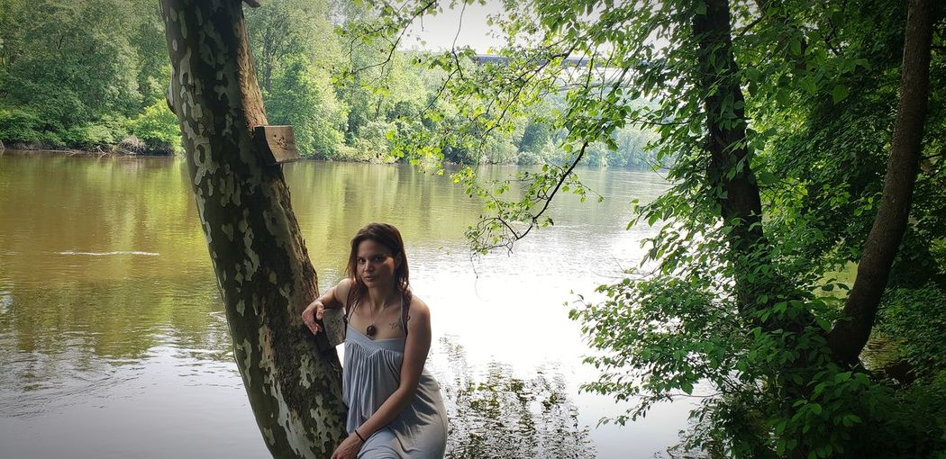 Portrait of young woman sitting on tree trunk against lake