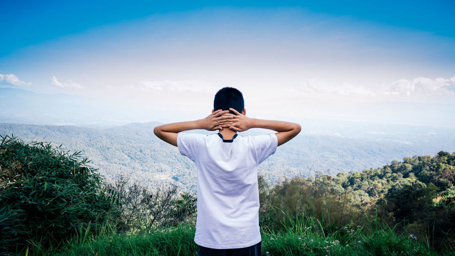 Rear View Of Man With Hands Behind Head Looking At Mountain