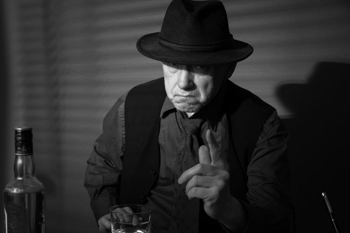 Film Noir reloaded: The dirty old detective in his bureau talking to a new client Acting Adult Hat Alcohol Bad Habit Bottle Day Detective Drink Front View Holding Indoors  Monochrome Old Person Old Person Sitting One Man Only One Person Real People Studio Shot