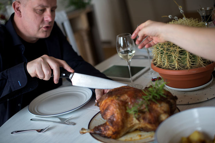 High angle view of family eating meat on dining table at home