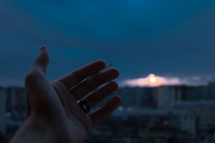 Close-up of hand holding cigarette against sky at night