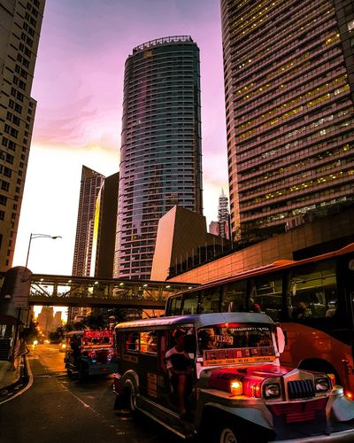 Cars on street by illuminated buildings against sky during sunset