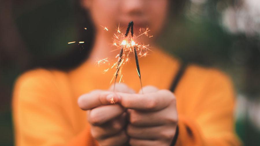 Cropped image of hand holding sparkler