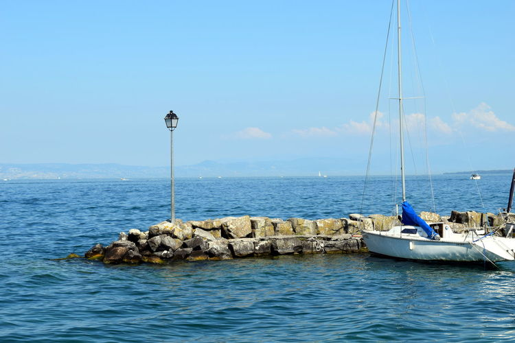 Blue Boat Day Lamppost Mast Nautical Vessel No People Remote Sailboat Sky Tranquil Scene Tranquility Water