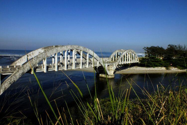 Bridge Over Calm Sea Against Clear Blue Sky