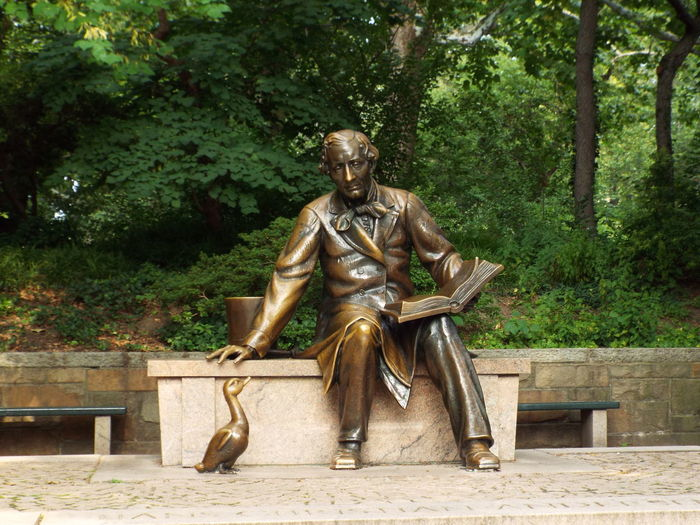 Statue of man sitting on bench in park